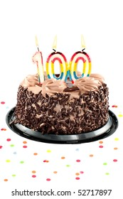 Chocolate birthday cake surrounded by confetti with lit candles for a century, one hudredth birthday or anniversary celebration