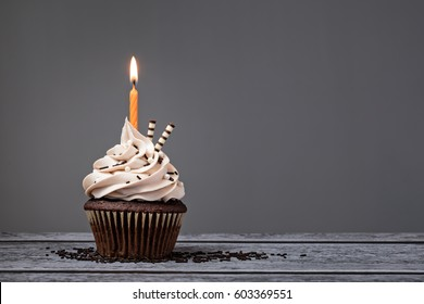 Chocolate Birthday cupcake with  buttercream icing and orange candle over a grey background.