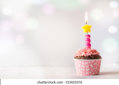 Chocolate Birthday Cupcake with Pink Frosting and Star Candle on Light Bokeh Background with Copy Space