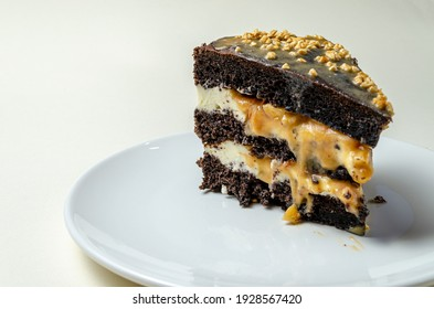 chocolate biscuit cake with nuts. with condensed milk on a white platter High quality photo