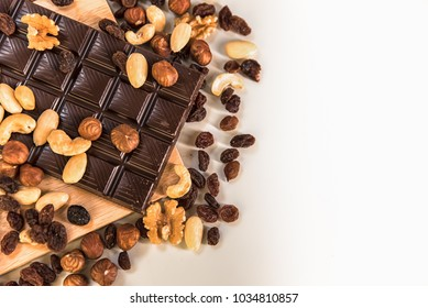 Chocolate. Black chocolate. A few cubes of black chocolate . Chocolate slabs spilled from grated chockolate powder.nuts