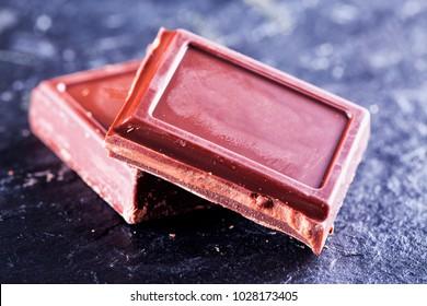 Chocolate blocks over black stone, horizontal image