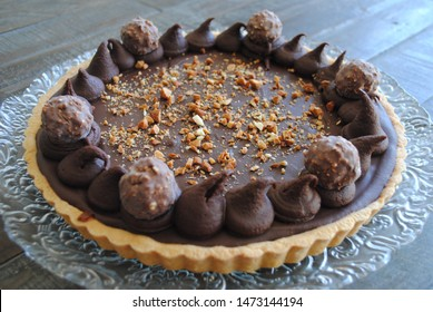 Chocolate and bombon filled pie with vainilla crust served on a glass plate over a white and blue cloth on wood table