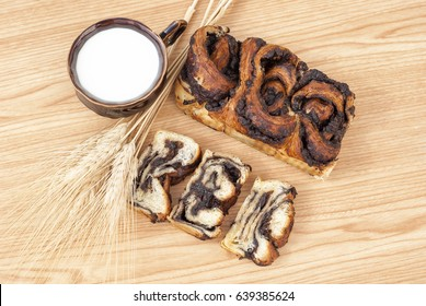 Chocolate braided bread / yeast cake , milk and wheat  on a wooden table.Symbol harvest, happy morning and Jewish holiday - Shavuot.Top view.