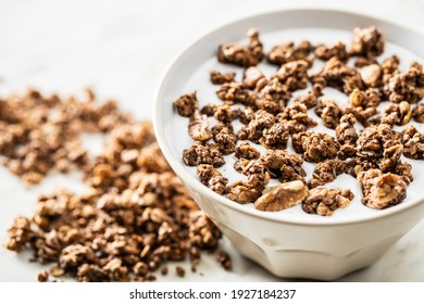 Chocolate breakfast cereal. Morning granola with milk in a bowl.