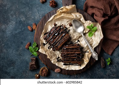 Chocolate brownie cake, dessert with nuts on dark background, directly above