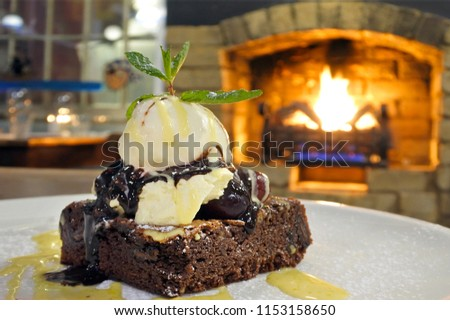 Chocolate Brownie cake served on a plate with vanilla ice cream against a warm fireplace.
