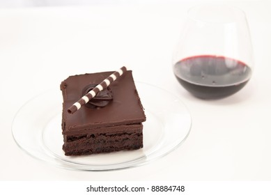 chocolate brownie on a white table with a glass of red wine in the background isolated on white