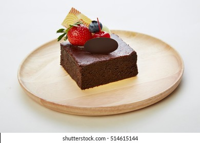 Chocolate Brownie on wood plate topped with mix strawberry, cheery, blueberry