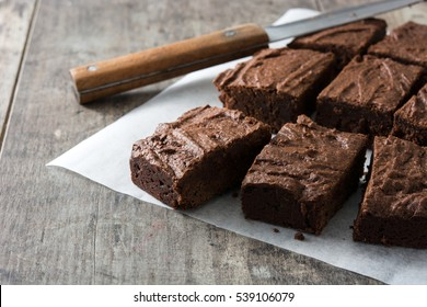 Chocolate brownie portions on wooden background