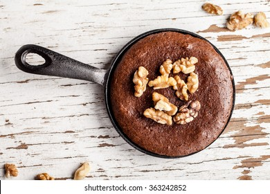 Chocolate brownie topped with walnuts in a cast iron skillet top view