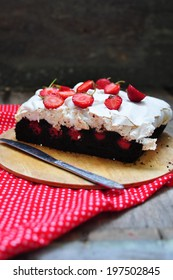 Chocolate brownies with meringue and strawberries, selective focus