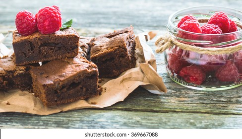 Chocolate brownies with raspberry on a wooden background