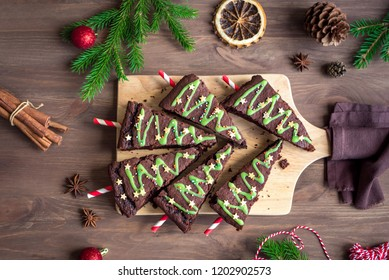 Chocolate Brownies in shape of Christmas Trees with green icing and festive sprinkles on wooden table, top view. Sweet homemade Christmas or winter holidays pastry food concept.