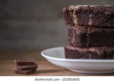 Chocolate brownies stacks on wooden background, homemade sweet and dessert