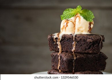 Chocolate brownies stacks and vanila ice cream on top, wooden background