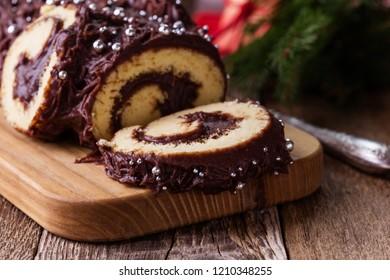 Chocolate Buche de Noel log on cutting board, Christmas chocolate roll dessert