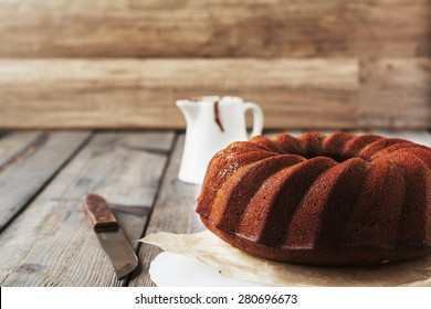 Chocolate Bundt cake with chocolate glaze on an old wooden table background. Selective focus.