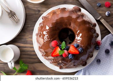Chocolate bundt cake with melted chocolate and frozen berries . Top view