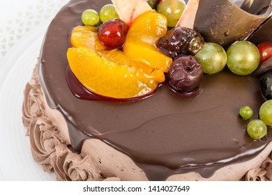 Chocolate cake with assorted fruits glazed tambourine and cocoa whipped cream on the side detail