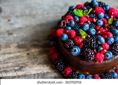 Chocolate cake with berries on wooden background