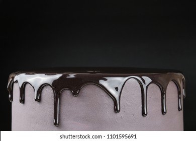 Chocolate cake with black glaze on a black background. Picture for a menu or a confectionery catalog.