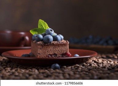 Chocolate cake with blueberries and mint on a brown plate.