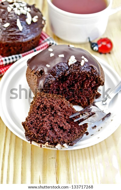 Chocolate cake, broke a fork on a white plate, cup of tea, a toy on a wooden board