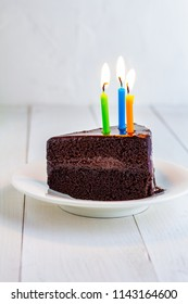 Chocolate Cake with candles on white plate.