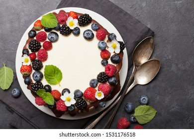 Chocolate cake or cheesecake with berries. On stone table with copy space. Top view flat lay