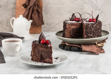 Chocolate cake with cherry cut on the cake stand and the piece lies on a light plate and a white background. Side view with a copy of the text space. Horizontal orientation.