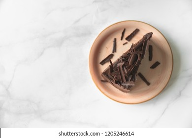 Chocolate Cake and Coffee.Chocolate cake on pink plate.Cake on white marble background.