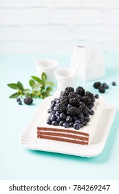 Chocolate cake with cream, blueberries and blackberries, selective focus