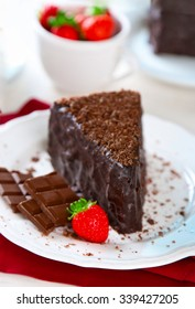 Chocolate cake with chocolate cream and fresh strawberries on plate, on light background