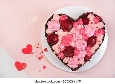 chocolate cake with cream in the shape of a heart on a pink background. St. Valentine's Day. top view