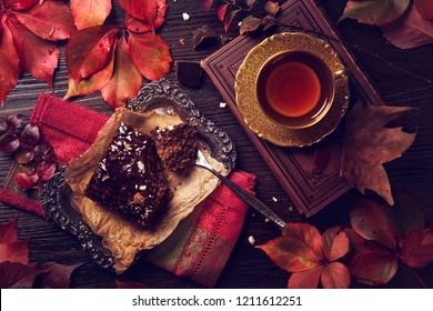 Chocolate cake and a cup of tea on a wooden background