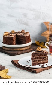 The chocolate cake is cut on the cake stand and the piece lies on a light plate and a white background. Side view with a copy of the text space. Vertical orientation.