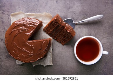 Chocolate cake with a cut piece and blade and cup of tea on gray background, closeup