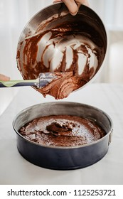 Chocolate cake dough being transferred into round-shaped baking tin with silicone spatula. Woman preparing chocolate cake to be baked. White background.