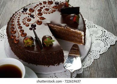 Chocolate cake with fresh strawberry and cup of tea on wooden rustic background. Fresh birthday berry fruit tart.