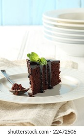 chocolate cake and fudge, decorate with mint leave, pile of dish behind.