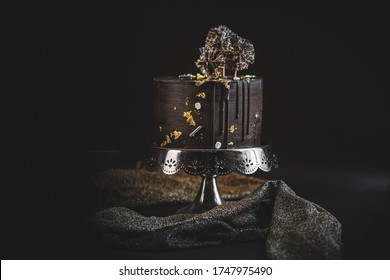 Chocolate cake with gold decoration on silver stand