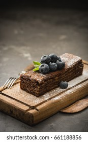 Chocolate cake with honey cream. The decoration on the cake strawberry. Cake on a wooden Board, a loft-style and rustic. Environmental products. Eco food.