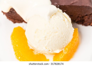 Chocolate cake with ice cream scoop on a sliced orange. Macro. Photo can be used as a whole background.