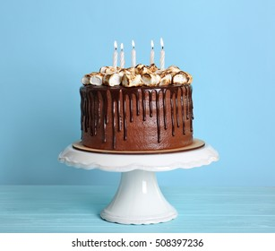 Chocolate cake with marshmallow on plastic stand on blue background