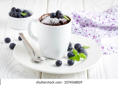 Chocolate cake in a mug with blueberry and powdered sugar, delicious summer dessert