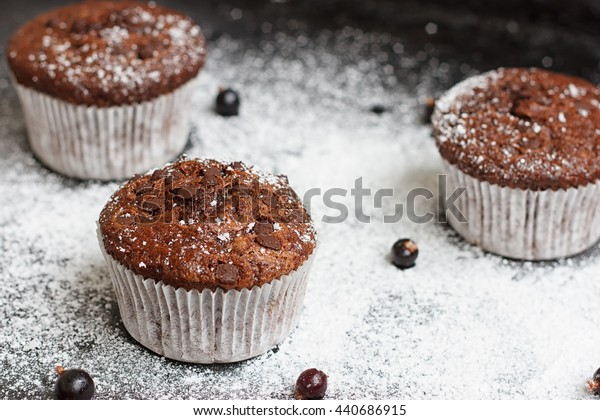 Chocolate cake on a black table with powdered sugar