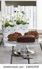 Chocolate cake on glass stand, on grey wooden table