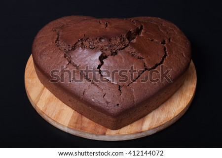 Chocolate cake on light wooden cutting board on black background. Heart shape.