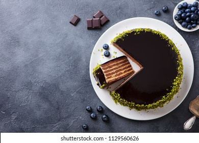 Chocolate cake on a plate. Grey stone background. Top view. Copy space.
